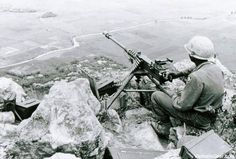 A machine gunner of the 101st Airborne sits with a commanding view near Tuy Hoa (II Corps).    Photo taken: August 1966