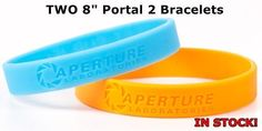 """Up for sale is the pair of bracelets pictured. What you see is what you will be receiving. The bracelets are 8"""" in circumference. One orange and one blue, both bracelets read APERTURE LABRATORIES TEST"""