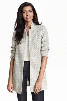 Manteau en jacquard de coton mélangé. Modèle avec col droit et poches devant. Sans boutonnage. Non doublé.