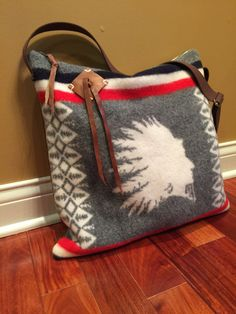 Genuine Pendleton®Wool blanket fabric was used to make this Chief bag. The opposite side is buttery soft leather. The bag is 17 tall and 17 wide. There is a generous 9 x 6 1/2 outside leather pocket that secures with a magnetic closure. The pocket has a D ring with a 3 naturally shed deer antler. The wool front has a hand stitched leather conch with hand dyed leather tie. The lining is cream cotton canvas. There are 6 inside slip pockets and a leather attached metal key clip. The bag has an…