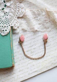 """Sweet Vintage Indie Sweater Guard by Silver Lining Decor. This charming and romantic sweater clip features pink floral clips and gold hued hardware.    Chain: 5.5"""" long"""