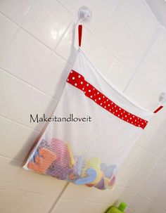 Dollar tree hack - buy a mesh laundry bag and some suction mounted hooks, voila! A new spot for little ones bath toys!