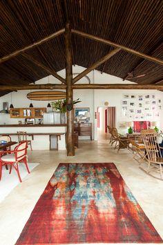 Nesta casa de praia no litoral paulista, sala e cozinha foram integradas pela reforma e a construção original ganhou mais quatro suítes. Os acabamentos seguiram o estilo rústico e a decoração foi composta de peças herdadas e garimpadas em feirinhas