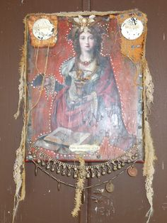 Mary Magdalene. FOund object with acrylic ,beeswax, antique fiber, rusty antique metal from old bread box.Her crown is a mid century earring and tow VERY old hand forged nails. Canvas has 1950s coins from India at the bottom and sterling belly dancers anklet.Sold