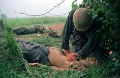 A corpsman (an enlisted soldier trained to give first aid and minor medical treatment) tries to help wounded Marines in Vietnam in Sept. 1966.