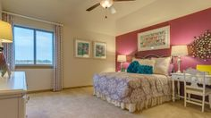 The pink wall and floral accents add girlish charm to this bedroom by Darling Homes at Bridges of Las Colinas. #girlsroom #girlsbedroom #paintingbedroom #pinkpaint #floral