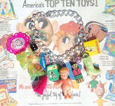 Armband - bracelet TOYZZZ bedelarmband met kleine vintage en retro speeltjes.  Handgemaakt armbandje van metaal met:  - neonroze hangertje met retro afbeelding - dobbelsteentje - gele barbieschoent...