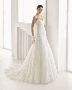 Vestido de novia silueta de guipour y encaje pedrería y escote corazón, en color natural.