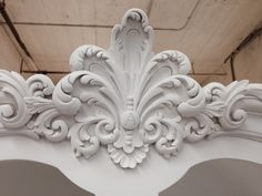 Detail of Hand carved fleur bonnet on built in china cabinets for a Boiserie dining room. Shown here undercoated & ready for hand glazing. Manufactured & designed by Auffrance.