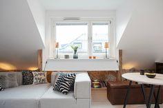 Zweeds huis met een bijzonder gave, zwevende trap. Detail wit plafond/bakstenen muur - Roomed | roomed.nl