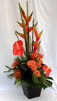 Fall Table Arrangement featuring orange Pincushion, orange Roses, Heliconia, Anthuriums, Brazilia berries and fancy greens.