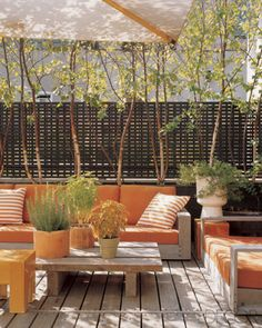 White birch trees shade a Sutherland sofa and love seat on the rooftop terrace; the cushions and pillows are covered in Perennials fabrics, and Booth designed the lattice screening.
