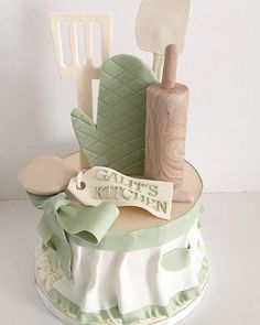 Kitchen themed bridal shower cake with fondant apron, rolling pin, oven glove, spatulas, and wooden spoon.