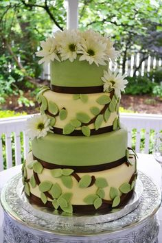 Leafy green four tier fondant wedding cake lined with chocolate brown ribbon and a white Daisy topper. By Party Delights in Raleigh, NC