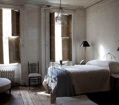 I love the antiqued, rustic, yet minimalist look, and this bedroom pulls it off so well! The chandelier is a nice touch as well.
