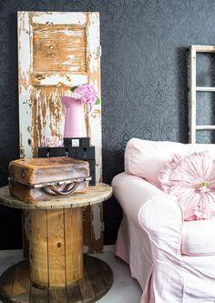 Mitä jos muuttaisit vanhan esineen käyttötarkoitusta? Kaapelikelasta tulee mainio pöytä ja ovesta seinäkoriste. Moderni, hieman muovisen oloinen tapetti korostaa komeasti puupintojen herkkyyttä.
