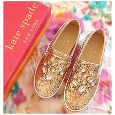 Kate Spade sneakers Gold glitter Kate Spade slip on sneakers with clear stones. These are very sparkly! Only worn a few times and there isn't any wear except on the bottom. All of the glitter and stones are perfectly intact. The white trim is clean without any marks. There is one mark on the inside of one shoe. See picture above. kate spade Shoes Sneakers