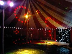 inside red and white oval big top party tent with disco lights