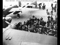 USAAF aircrewmen preparing .50 caliber machine gun ammunition on the flight deck of USS Hornet (CV-8), while the carrier was steaming toward the mission's launching point. Three of their B-25B bombers are visible. That in the upper left is tail #s 40-2298, mission plane # 6, piloted by Lt. Dean E. Hallmark. That in top center is tail # 40-2283. It was mission plane # 5, piloted by Captain David M. Jones. Both attacked targets in the Tokyo area. Lt. Hallmark, captured by the Japanese in…
