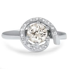 The Swansea Ring.  This stunning Retro-era ring showcases a beautiful round brilliant diamond within a distinctive open halo of accent diamonds and features elegant lines for a piece that is truly one of a kind.  [LOVE this ring. Looks beautiful on the finger.]
