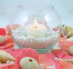 Perfect for the beach, this centerpiece features a votive candle nestled on a bed of pearls inside a round bowl. Description from my-wedding-reception-planning.com. I searched for this on bing.com/images