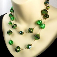This lovely vintage Vendome necklace features vibrant, green foil glass melon beads highlighting painted Saturn beads and aurora borealis faceted round glass beads strung on a gold tone chain with decorative bead ...