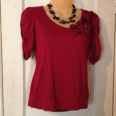 Red top with flower detail Cute dark red top, has ruched elbow length sleeves, flower detail that includes a red bead and black mesh. Worn several times but in good condition!  Size petite small. Necklace not included. Tops