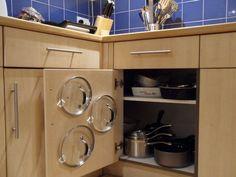 Que las tapas no se encimen, coloca ganchos de plástico en la puerta y acomódalas ahí. | 21 Brillantes ideas para organizar tu cocina de una vez por todas