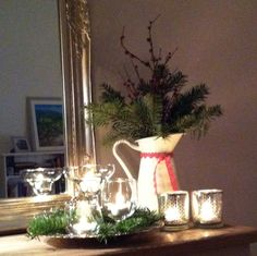 Pitcher with pine branches and candle lights