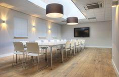 Interieur bouwbedrijf. Vergaderruimte. Flexibele oplossing voor bijeenkomsten gevonden in de vorm van losse tafels. Witte werkbladen op een verchroomd onderstel. Lichte, luchtige en stapelbare vergaderstoelen uitgevoerd met een kunststof rug en zitting, welke voorzien is van een meshstoffering. Maatwerklampen ter ondersteuning van de functionele verlichting om de opstelling een intiemere sfeer mee te geven.