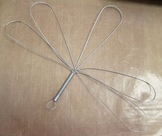 A blogger buys a $1 whisk at her grocery store. Using pendant beads, she creates THIS