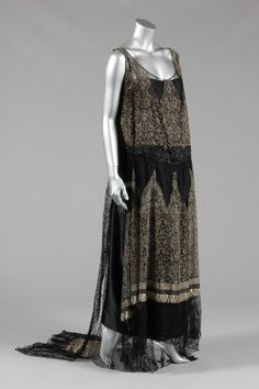 Maison Worth couture silver lace and black tulle evening gown, circa 1929, with narrow woven ivory signature label to the waist, the black tulle ground applied with pointed bands of silver lace with beaded waistband, floating panel forming a train to the back. Via Kerry Taylor Auctions.