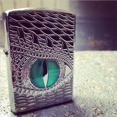 A dragon eye is deep carved into this high polish Armor™ lighter, its emerald green eye filled in with a brilliant epoxy inlay Zippo lighter