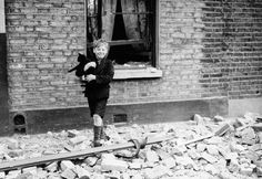 Young boy carries cat through the devastation of the London Blitz, early 1941.