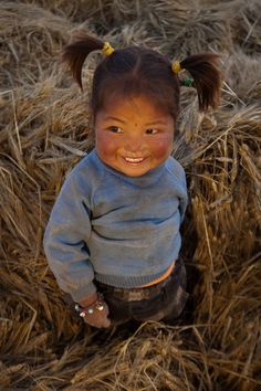 Tibetan girl playing at dusk amongst freshly cut wheat; Patrick, picto.asia