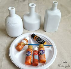 Using craft paint to upcycle bottles into hand-painted pumpkins and gourds for autumn decor by Sadie Seasongoods / www.sadieseasongoods.com