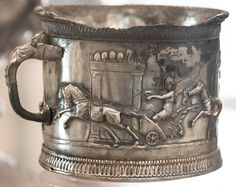 A single-handed cup with with a chariot race of amors in the Circus Maximus. Silver with traces of gilding. 1st century BCE—1st century CE. H. 8 cm, d. 9.5 cm, weight 355 g. Inv. No. 145510. Naples, National Archaeological Museum. Origin: The cup is a part of a silver deposit uncovered in the basement of the Casa del Menandro Pompeii in 1930. In the cellar, wrapped up in textiles and placed in the bottom of a wooden chest, were 118 pieces of silver plate, of varying ages and style