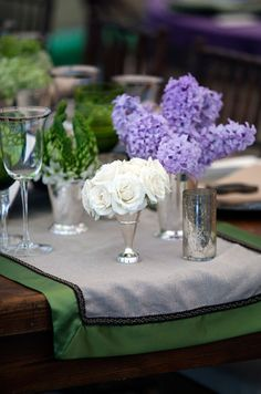 A wooden table with a gray and green runner is decorated with purple hyacinths, white roses and tea candles.
