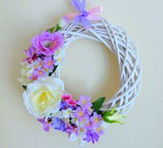 www.abgHomeArt.pl Wianek wielkanocny na drzwi. Ręcznie wykonany wianek wiosenny na podstawie z białej wikliny o średnicy 30 cm pełen kwiatów w różnych odcieniach różu, fioletu i bieli. Udekorowany między innymi kwiatami róży i fiołka, przyozdobiony satynową wstążką.  Efektowna i wyjątkowo elegancka dekoracja, która pięknie przyozdobi drzwi, okno, czy też kominek. Można go powiesić lub może służyć jako stroik. Idealny do każdego wnętrza.