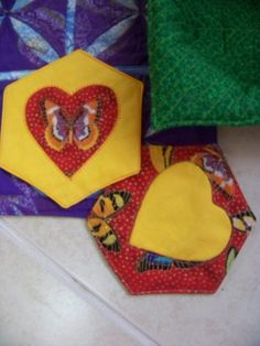 Julie Comstock's Hex and Heart Coasters. The one with the yellow heart is my first attempt and the one with the red my second. I got a little more adventurous with the second and fussy cut the butterfly, centred it from point to point instead of side to side and blanket stitched around it by machine.. I like them. You can get the pattern and tutorial from www.comsmocricket.typepad.com