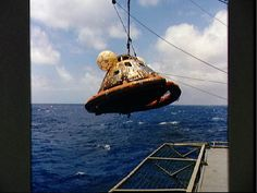The Apollo 11 spacecraft Command Module is photographed being hoisted aboard the U.S.S. Hornet, prime recovery ship for the historic lunar landing mission. Note the flotation ring attached by Navy divers is still attached to the capsule. (July 24, 1969)