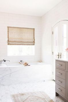 White and taupe bathroom features a taupe vanity topped with white marble atop a marble herringbone tiled floor layered with a taupe Persian rug.