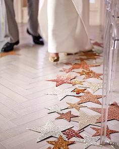 Glittery paper stars act as a runner and lead the way down the aisle.