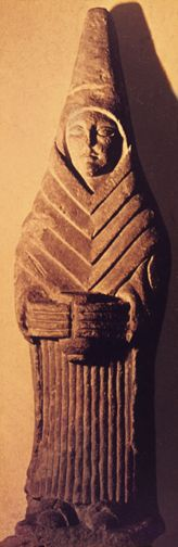 stylized sculpture of woman standing with offering cup and tall peaked headdress