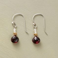A pair of pearl and garnet drop earrings, wherein Mozambique garnets are emphatic punctuation marks beneath cultured pearls and golden disks.