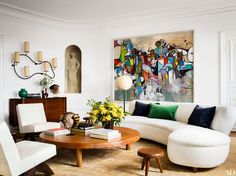 A Freeform wall light by Jean Royère undulates above the living room's George Nakashima sideboard, and a Vladimir Kagan sofa curves around the Pierre Chapo low table   archdigest.com
