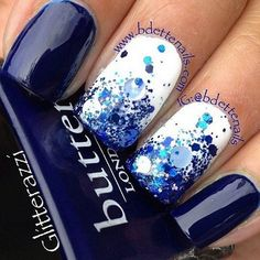 Exciting dark blue nail art with a twist. This nail art design looks like a wonderful splash of summer with the help of dark blue glitter and sequins added on top of a white polish background.