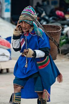 Yunnan China A Lahu woman, in traditional clothes, leggings & earrings and carrying a backstrap basket & shoulder bag, smoking a pipe while shopping at Nanmei market. We Are The World, People Around The World, Laos, Beautiful World, Beautiful People, Costume Ethnique, Costumes Around The World, Best Portraits, Folk Costume