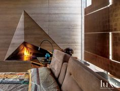 Rather than design the expected square or rectangular fireplace, Burnette created one in the shape of a faceted volumetric triangle, fabricated by The Construction Zone from mill-finished hot-rolled steel and rammed earth. The bed was designed by LeavittWeaver and upholstered in suede.