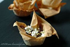Baskets of phyllo dough with caraway braised in red wine with onions, feta and pistachios